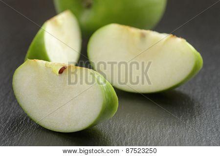 green sour apple on slate board sliced