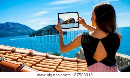 Woman traveler photographing St. Nikola island in Budva