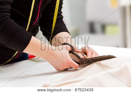 Dressmaker Cutting Fabric With Scissors