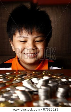 Young Boy Stacking or Piling Coins