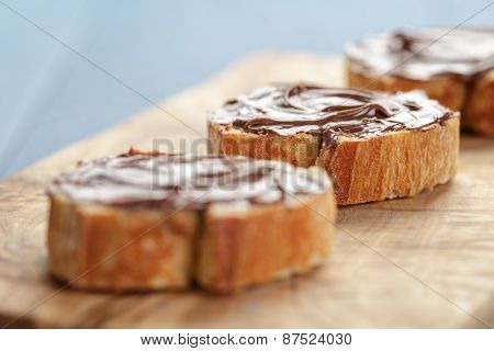 baguette slices with chocolate hazelnut spread on olive board