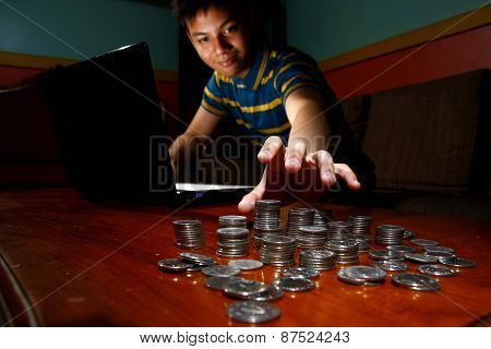 Asian Teen in front of laptop computer and reaching for a stack of coins