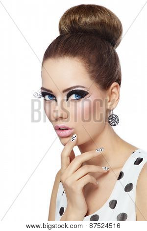 Young beautiful girl with fancy cat eyes and polka dot manicure over white background