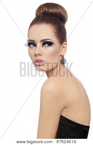 Young beautiful woman with fancy cat eye make-up and stylish hair bun over white background