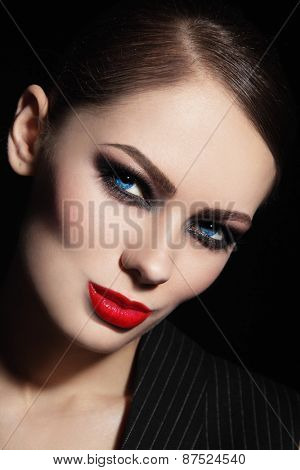 Portrait of young beautiful woman with smoky eyes and red lipstick