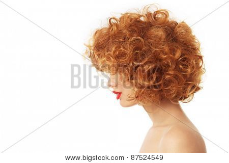 Profile portrait of young woman with beautiful red curly hair over white background