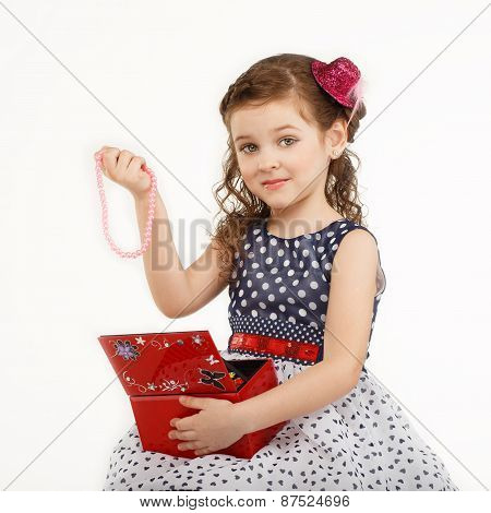 Little Girl Admires The Accessories In The Box