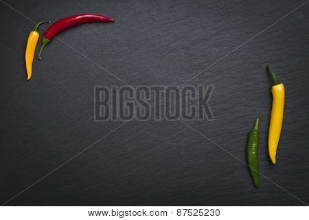 Four colorful chili peppers isolated on a slate stone slab with empty copy space.
