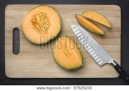 Chopped fresh musk melon on a cutting board on grey slate background, looking fresh and healthy.
