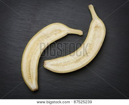 Two slices of cut banana isolated on dark stone background.