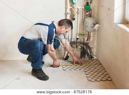 Man Worker Lays On The Floor Tiles