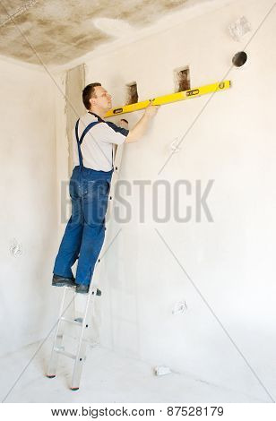 Man Worker Checks The Wall With A Level