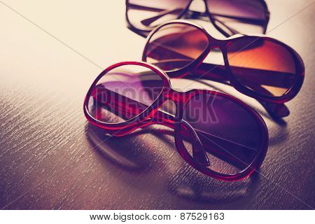Fashionable Sunglasses On Desk. Vintage Stylized.
