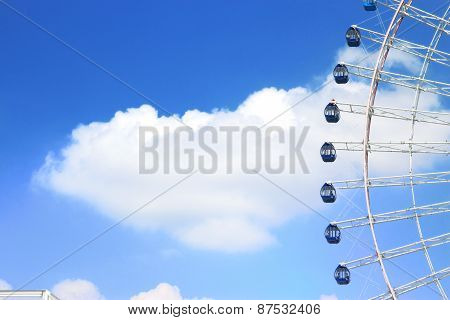 ferris wheel cab rotating high above the ground against a cloudy blue sky