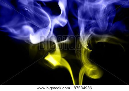 colored smoke on a black background with ukrainian flag