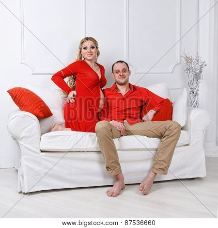 Happy young pregnant couple dressed in red embrace each other on a sofa in white living room
