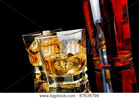 Two Whiskey With Ice In Glasses Near Bottle On Black Background