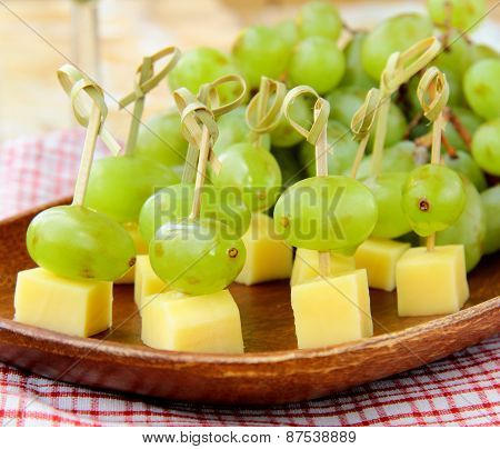 canape snack - cheese with green grapes on wooden skewers