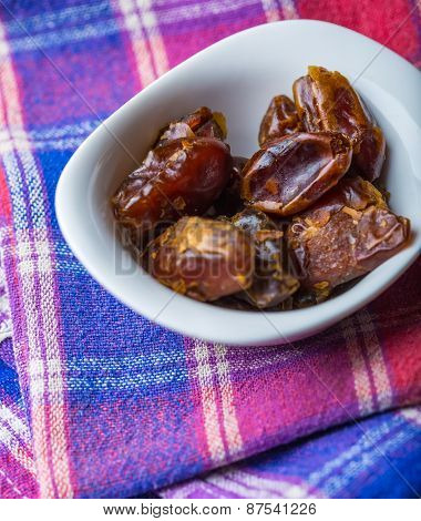 Dried Dates In Bowl On Wooden Table..
