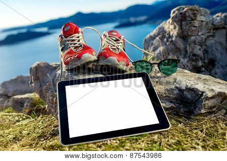 Digital tablet with shoes and glasses on the mountain