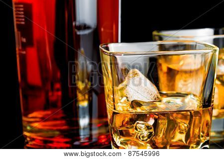 Close-up Of Whiskey With Ice In Glasses Near Bottle On Black Background