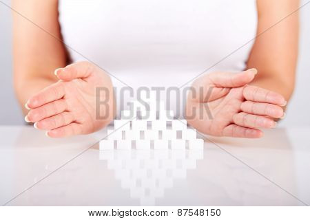 Female Hands Over A Pyramid Of Sugar Cubes
