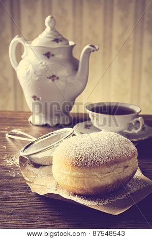 Closeup Shot Of Donut With Cup Of Tea On Table In Old-fashioned