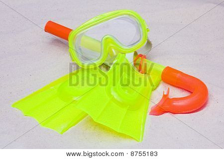 A Child's Sorkel, Mask And Flippers Laying On The Sand