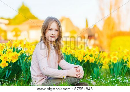 Adorable little girl playing with flowers in the park at sunset,