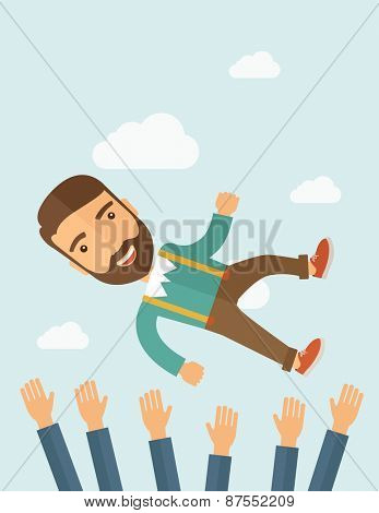 A successful smiling hipster Caucasian businessman being thrown in air.