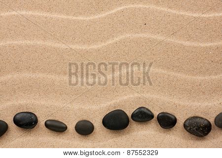 Black Stones Lie On The Sand