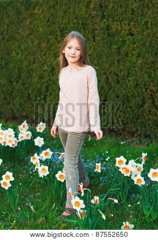 Cute little girl of 7 years old playing in the spring park between daffodils flowers