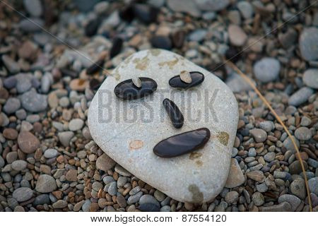 Funny face from marine rocks on the shore