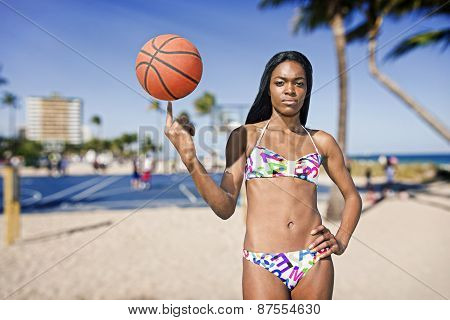Black woman with basketball on her finger, at a basketball field. Beach