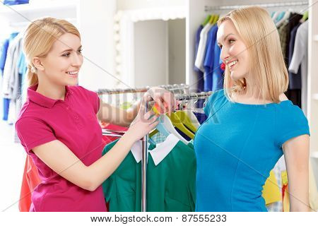 Customer talks to sales consultant by the clothing rack