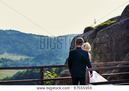 Groom Comes To The Bride Standing Near The Fence On The Mountain.view From The Backside