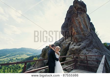 Bride And Groom Posing On The Mountain On A Sunny Day