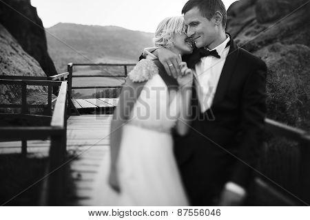 wedding couple walking on the bridge in the mountains
