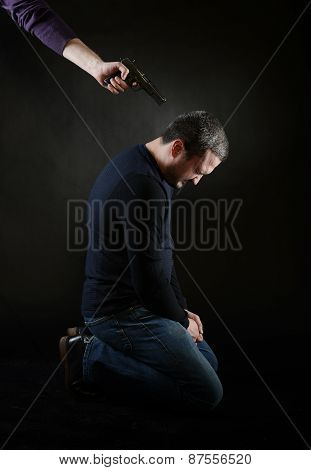 A Man On The Knees Under The Gun