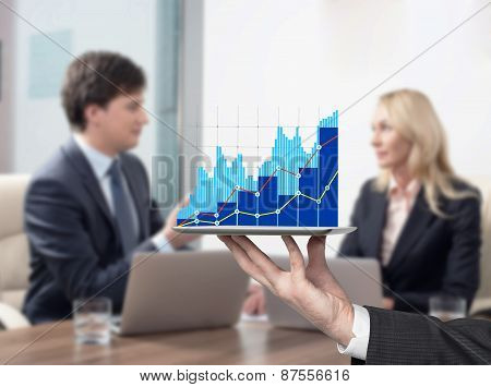 Young Couple At The Business Meeting. Bar Chart On The Device.