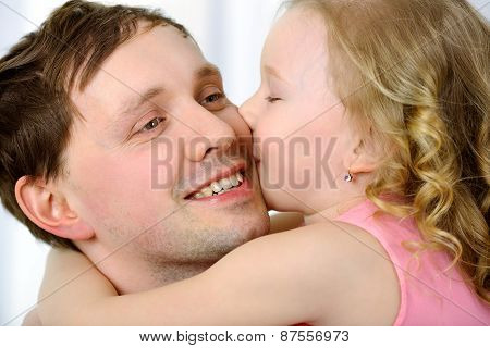 Little girl kissing fathers cheek