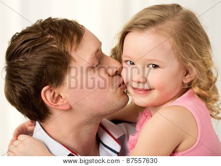 Daddy kissing beautiful little daughter