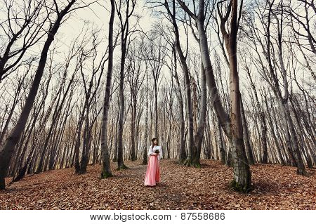 Beautiful Bride Outdoors In A Forest With Bouquet