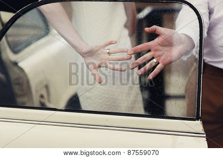 Two hand with rings on the car's glass