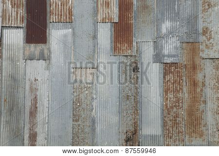 Grungy Corrugated Steel Wall With Rusty Spots On An Old Building