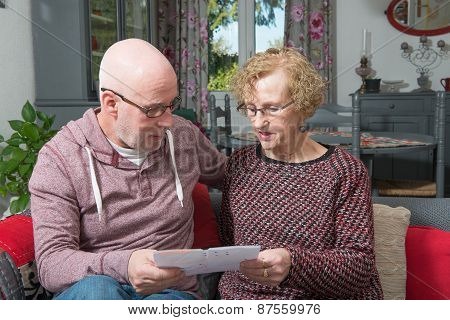 An Elderly Mother With Her Son Watching A Digital Tablet