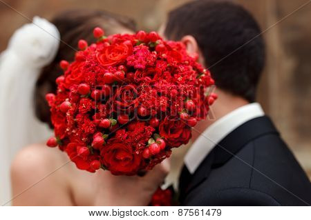 Wedding Couple Covering His Face With Bouquet Of Flowers.