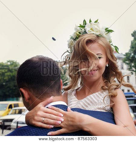 Handsome Bridegroom Carrying His Beautiful Laughing Bride In His Arms
