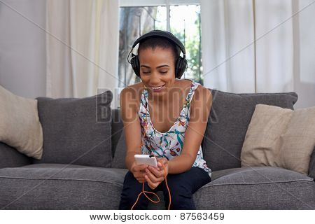 mobile cellphone young woman listening music sofa couch at home living room