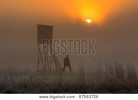 Man Standing Near Raised Hide At Sunrise